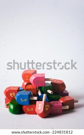 Pile Of Dreidels On White Background For Hanukkah - stock photo