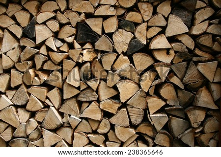 Pile of dried chopped firewood stacked for winter. Nice firewood background. - stock photo
