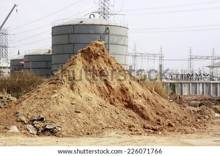 Pile of dry soil and sand in front of big Industrial tanks