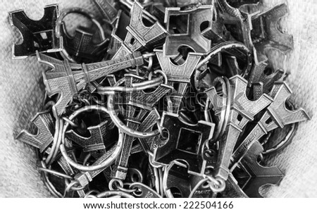 Pile of Eiffel Tower trinkets in the wicker basket. Typical souvenir from Paris. Aged photo. Black and white.