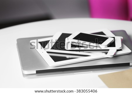 Pile of electronic gadgets on the table. Communication and technology concept - stock photo