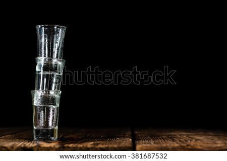 Pile of empty shot glasses (close-up shot) on wooden background - stock photo