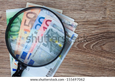 pile of euro banknotes under looking glass - stock photo