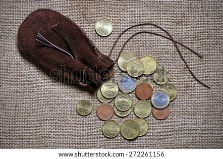 Pile of euro coins spilling out of a drawstring pouch onto a rustic old burlap - stock photo