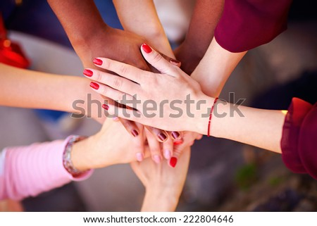 pile of female multiracial hands in union sign - stock photo
