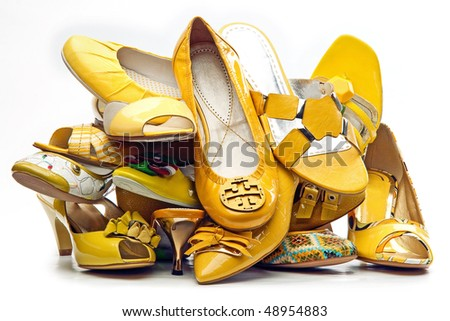 Pile of female yellow shoes isolated on white background - stock photo