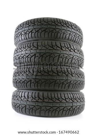 Pile of four winter car tyres shot on white - stock photo