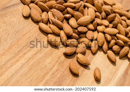 Pile of fresh almond nuts spread out on wooden surface