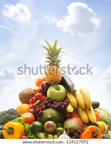 Pile of fresh and tasty fruits and vegetables over the sky background - stock photo