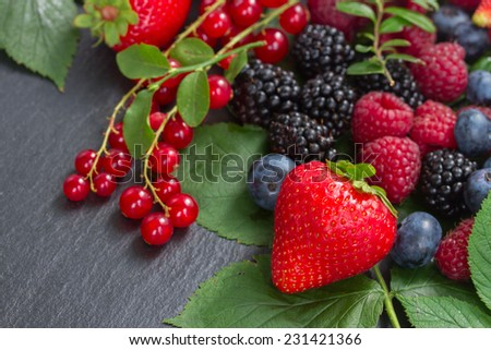 pile of fresh  berries with green  leaves   on black stone  - stock photo