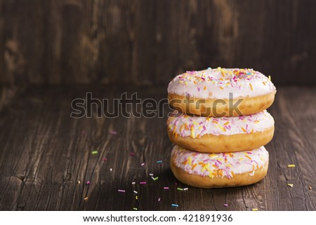 Pile of fresh homemade donuts with icing and colorful sprinkles - stock photo