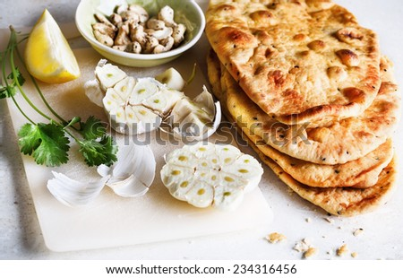 Pile of freshly baked flat bread and spices on a table - stock photo
