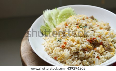 Pile of fried rice in the white plate with slice lime and cucumber on a wooden table