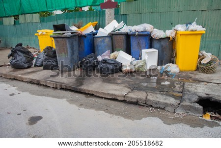 Pile of garbage and overfilled recycle bins - stock photo