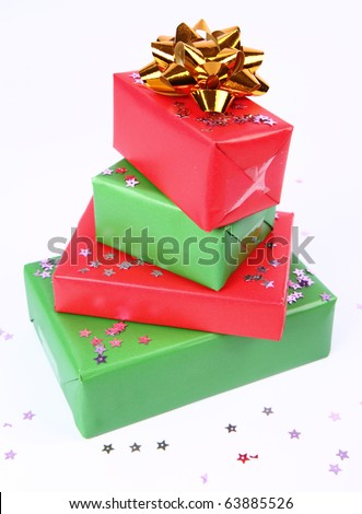 Pile of gifts in green and red wrapping with a golden bow decorated with star shaped confetti - stock photo
