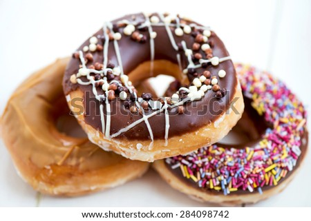 Pile of Glazed Doughnuts with colourful sprinkles, chocolate, icing on top of them. White background - stock photo