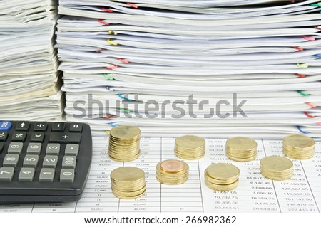 Pile of gold coins with calculator and pile of paperwork as background. - stock photo