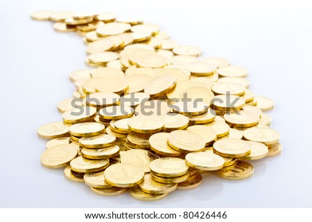 Pile of golden coins on a glossy grey surface. Coins of ten roubles.