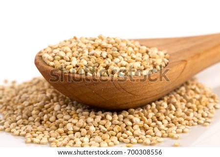 Pile of grain quinoa seeds in spoon isolated over the white background