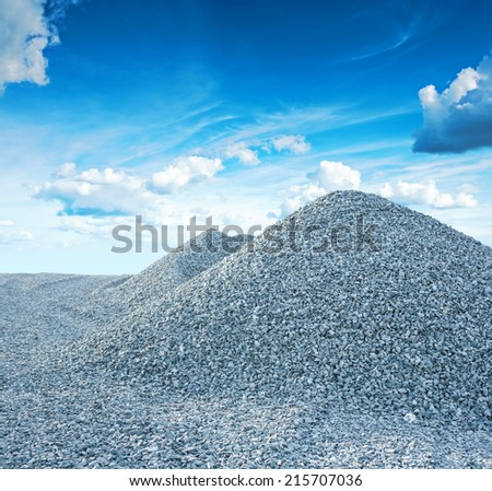 pile of granite gravel on background of the sky - stock photo
