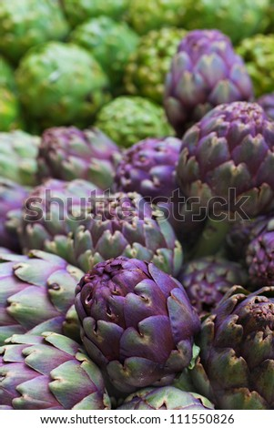 Pile of green and purple Italian Artichokes at the farmers market