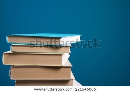 Pile of hardcover books on blue background, education and knowledge concept. - stock photo