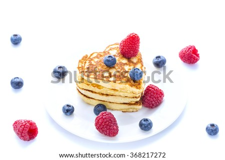 Pile of heart shaped pancakes with blueberries and raspberries on white background - stock photo