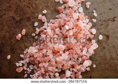 Pile of Himalayan pink salt, top view on rusty metal background - stock photo