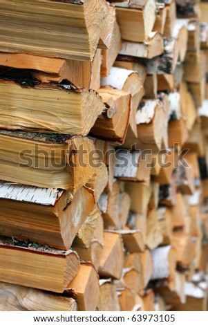 Pile of irregularly stacked pieces of firewood. Focus on one edge - stock photo