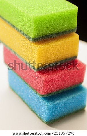 Pile of Kitchen Colorful Sponges On White Surface Against Black Background. Vertical Image Composition - stock photo