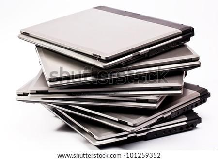 Pile of laptops on the white background - stock photo