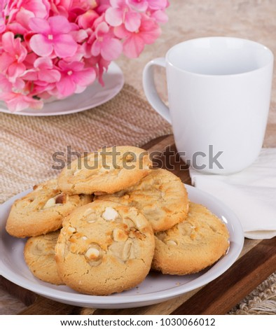 Pile of macadamia nut cookies on a plate with coffee cup and flowers in background