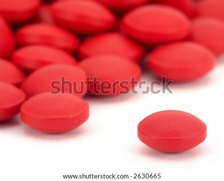Pile of many small red pills, with one isolated on white in the front. - stock photo