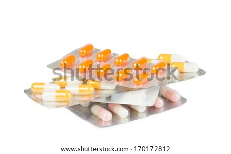 pile of medicine pills and capsules packed in blisters isolated on white table - stock photo