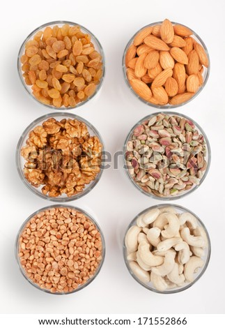 Pile of mix collection of dry fruits in glass bowl over white - stock photo