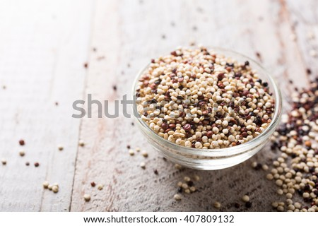 Pile of mixed raw quinoa, South American grain, in glass bowls on white rustic wooden background. Healthy and gluten free food. Copy space. - stock photo