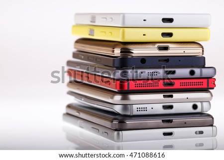 Pile of mobile phone. Heap of the different smartphones isolated on white background.