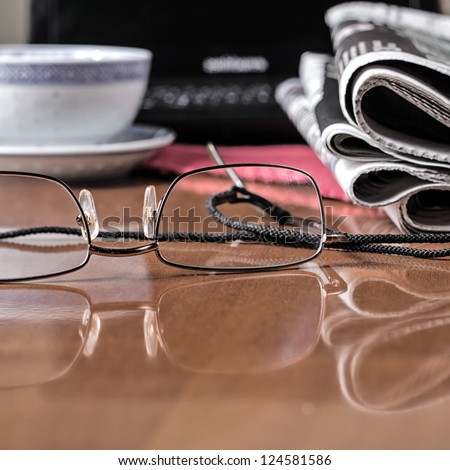 pile of newspaper & glasses on table - stock photo