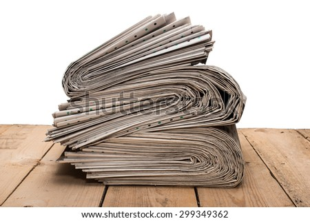 Pile of newspapers on a wooden table,  on white background - stock photo