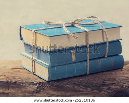 Pile of old blue books on a wooden table - stock photo