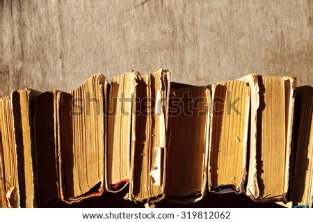 Pile of old books. A number of old books on a wooden surface close up - stock photo