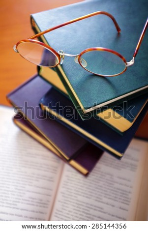 Pile of old books and a pair of vintage glasses on top - stock photo