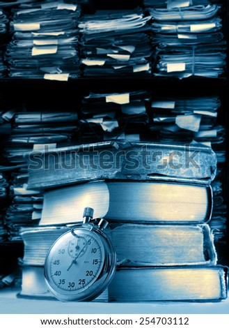 Pile of old books and stopwatch on archive folders background - stock photo