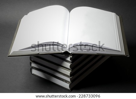 pile of old books on light table, one book opened with copy space, black background  - stock photo
