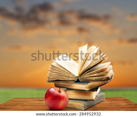 Pile of old books with apple on sky background
