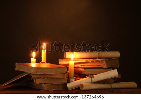 Pile of old books with candle and scroll in dark