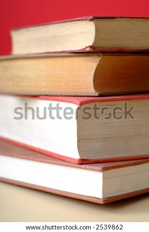 Pile of old books with covers and white pages with red background - tighter crop