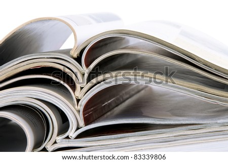 pile of old magazines with bending pages on white background - stock photo
