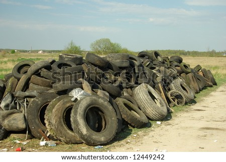 Pile of old tires near the road - stock photo