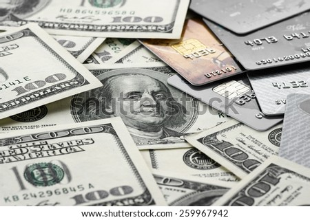 Pile of one hundred dollar bills and plastic cards close-up. - stock photo
